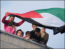 Family watch Palestinian football match from nearby building
