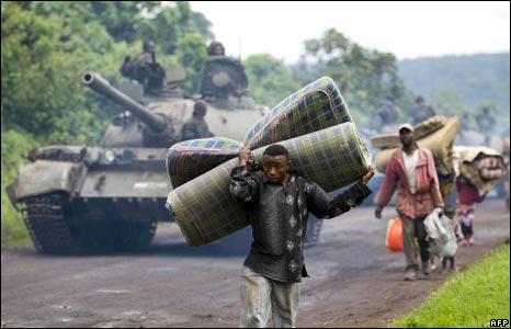 A man carrying a mattress passes a Congolese army tank
