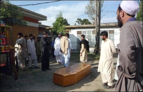 """Pakistani security officials stand near a coffin containing the body of security person who was reportedly killed by Taliban militants at Saidu Sharif hospital in Pakistan""""s troubled Swat valley on Wednesday, Oct. 22, 2008"""