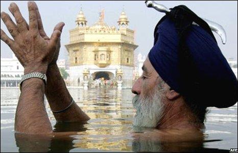 A Sikh man prays submerged in water