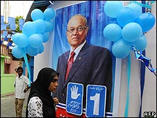 Woman walks past electoral poster for President Gayoom in Male on 26/10/08