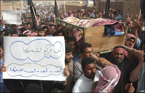 Crowds carry the coffin of a victim