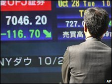 A passer-by looks at an electronic stock board in downtown Tokyo, Japan