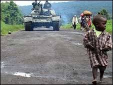 A boy in DR Congo running in front of a tank