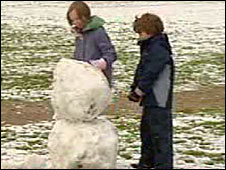 Children building a snowman in Aviemore, Scotland