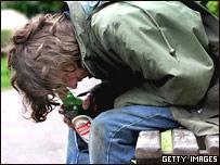 Мужчина сидит с пивной бутылкой, низко опустив голову