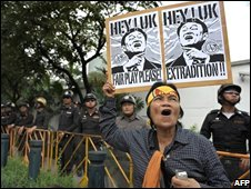 An anti-governement protester holds up a placard showing images of ousted Thai prime minister Thaksin Shinawatra