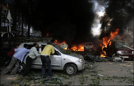 Cars burning at the site of an explosion in Guwahati, Assam