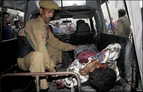 Police taking an injured blast victim to hospital in Guwahati, Assam