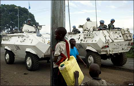 UN armoured vehicles drive past two young boys in Goma