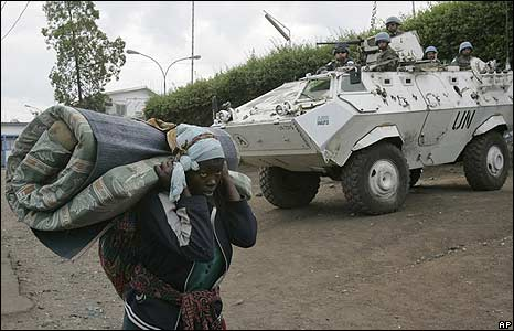 A displaced Congolese woman walks past a UN armoured vehicle in Goma