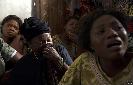Mourners cry near the bodies of two women allegedly killed by Congolese soldiers