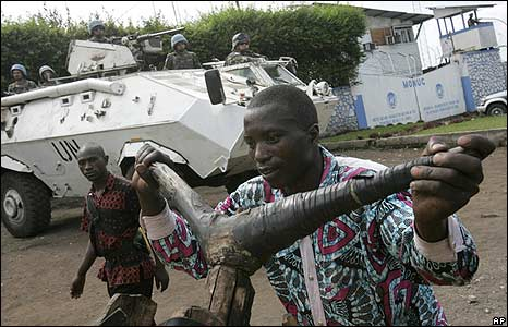 A displaced Congolese man pushes a wooden bike past UN troops in Goma