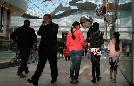 Young girls holding ballons while window shopping in Westfield