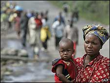 Woman and child walking with other civilians walking behind