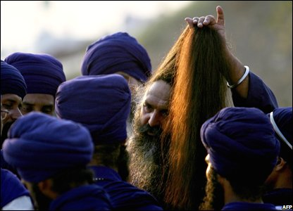 A Sikh man arranges his hair on the banks of Godhavari river in Nanded,