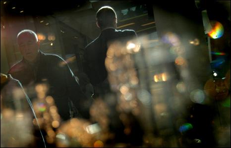 Shoppers reflected in in window dsilpay