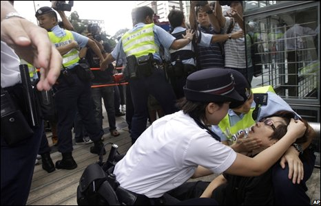A woman is tended by police during a protest in Hong Kong about investments linked to failed US bank Lehman Brothers.