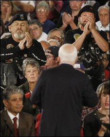 Two men who identified themselves as Vietnam veterans applaud as Republican presidential candidate, Sen. John McCain