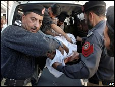 Police carry a person injured by the suicide bomb