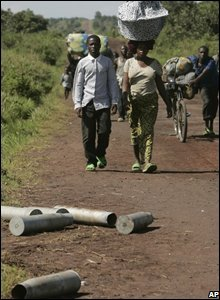 Displaced people walk past spent ammunition near Kibumba on 31 October 2008