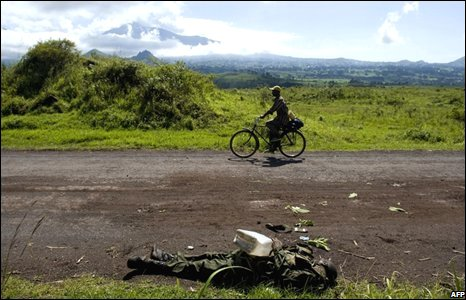 A man cycles next to the corpse of a Congolese soldier near Kibumba on 31 October 2008