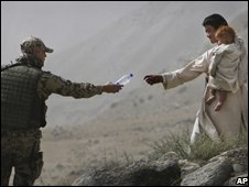 Isaf soldier offers water to Afghan man