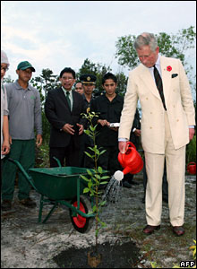 Charles waters a newly planted tree at the Simpan Badas forestry, Brunei