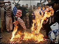 Iraquíes queman una bandera de Estados Unidos.
