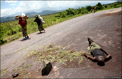 Women pass a corpse on a road outside Goma