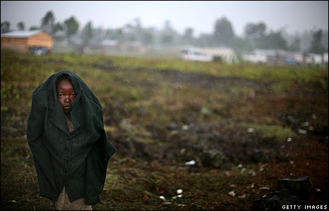 A boy shelters from the rain at a refugee camp near Goma