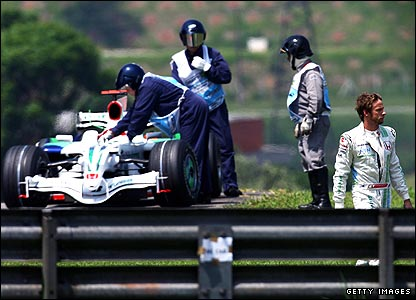 Jenson Button leaves the track as his Honda is rescued