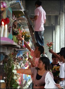 People light candles and place flowers in front of a communal tomb in a Manila cemetery, the Philippines, 1 November 2008