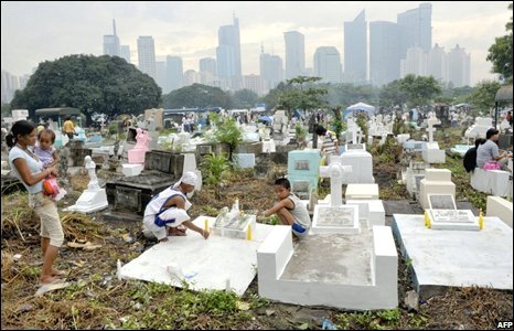 Relatives light candles at the graves of deceased loved ones in Manila, the Philippines
