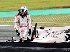 David Coulthard walsk away from his wrecked car in the Brazilian Grand Prix
