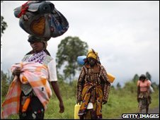 Displaced Congolese women carry their belongings as they leave a camp outside Goma, 2 November 2008