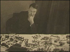 Adolf Hitler looks at a model of Linz