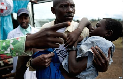 A malnourished child is carried by a Congolese Red Cross worker