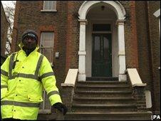 Security guard outside Fernando Gomez's workshop in Hackney