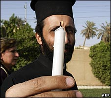 An Iraqi Greek Orthodox priest holds a candle at a demonstration for minority rights in Baghdad