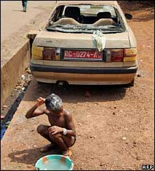 Girl washing her hair on the road in front of car destroyed in riots last year (file photo)