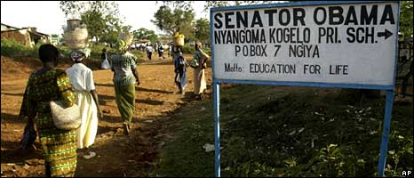 Resident in Kogelo walk past a sign to the village's Senator Obama Primary School