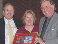 Hellen Bach and Norman Macintosh are presented with a gold disc by Sir Terry Wogan