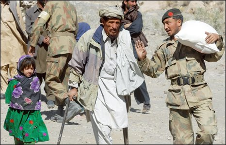 A Pakistani army soldier (R) carries a relief supplies as he helps a disabled earthquake survivor (C) at a hilly area of Wam, one of about eight sparsely populated villages surrounding the town of Ziarat that were worst-hit by an earthquake, on November 4, 2008.