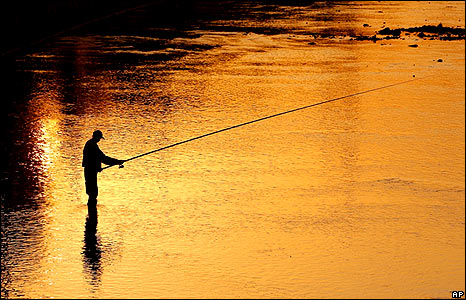 A man fishes at sunset in the Somesul Mic river in Cluj, central Romania.