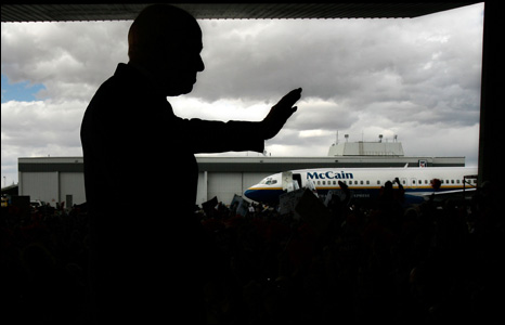 Sen. John McCain (R-AZ) waves from inside an airplane hanger during his last campaign rally