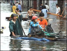 A girl and her bicycle are carried on a raft through a flooded street in Hanoi, Vietnam on 4 November 2008
