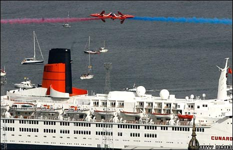 The Red Arrows fly past the QE2, berthed at the Ocean Terminal in Greenock, Scotland, in September 2007.