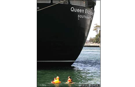 Two pranksters on rubber duck buoys return to land after attacking the QE2 with fake swords at Circular Quay in Sydney, Australia, on 22 February 2007.