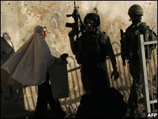 Palestinian woman looks at Israeli troops in Silwan